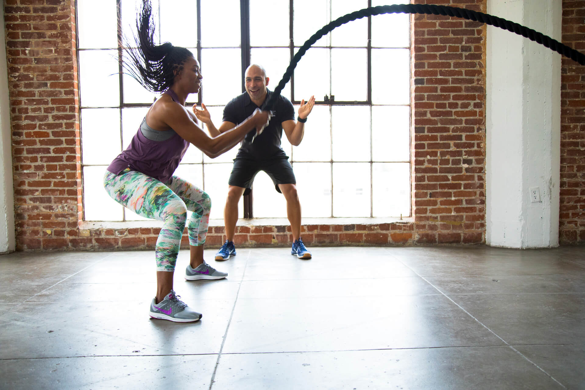 Personal Trainer Encourages Woman Using Battle Ropes